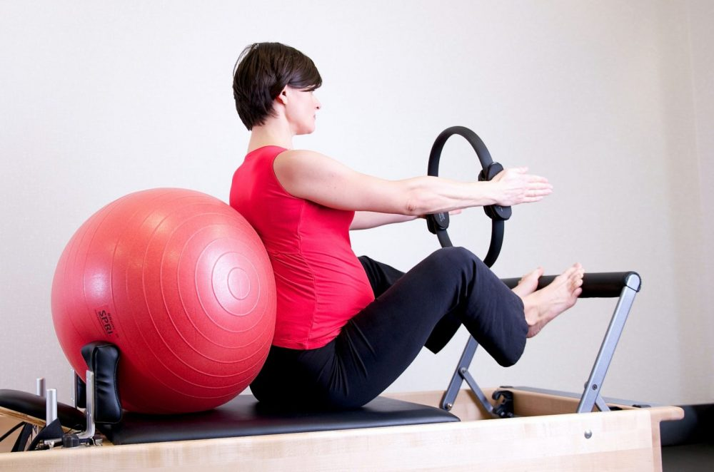 woman-in-red-top-leaning-on-red-stability-ball-1103254
